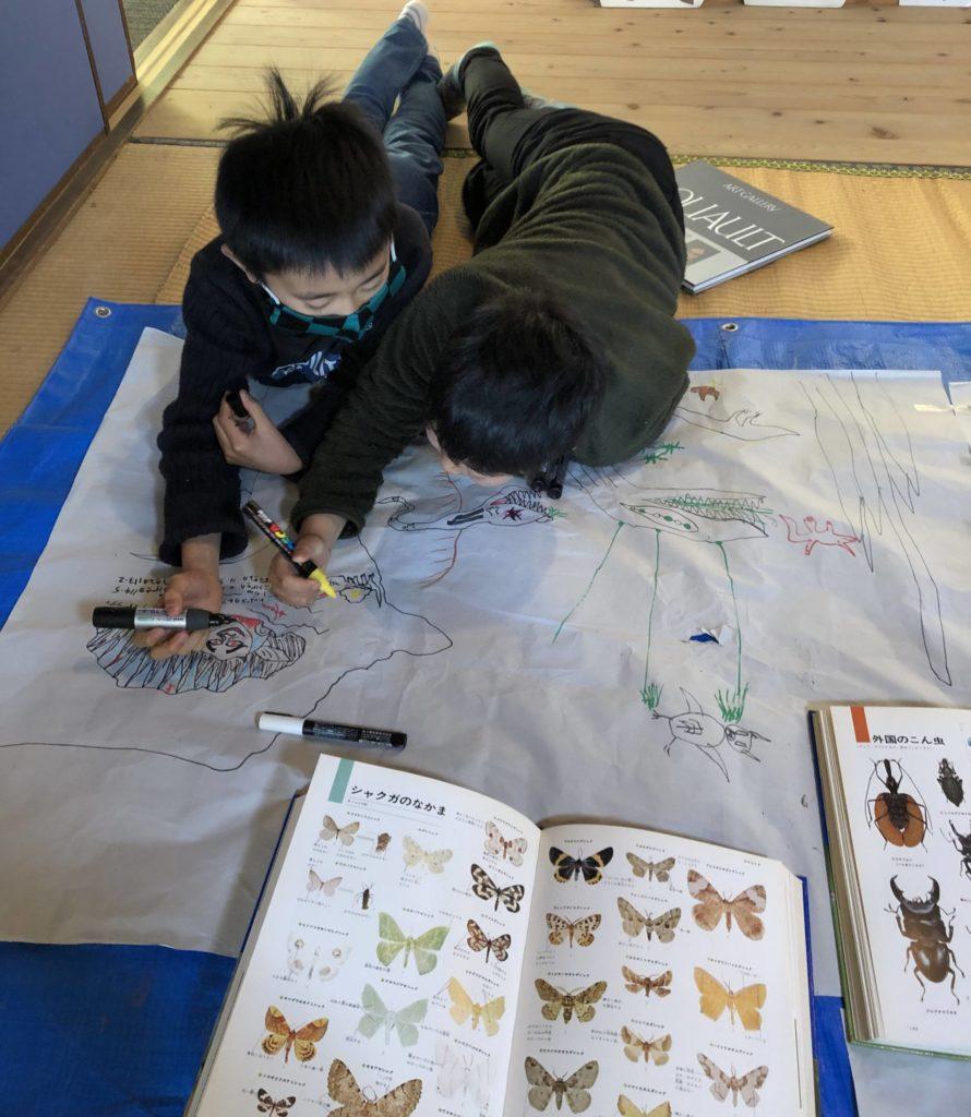 絵を2人で描く子供たち